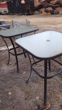 Two glass top patio tables with brown steel frames 44 inch tall