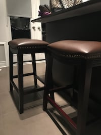 Two brown faux leather padded counter height stools