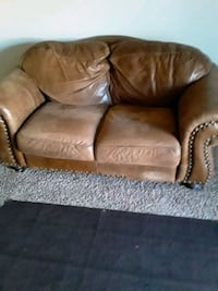 Leather loveseat with area rug,tall lamp,wallclock