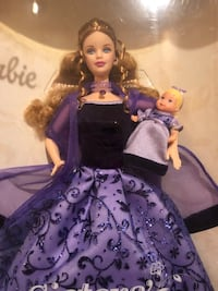 Barbie in purple floral dress carrying baby doll