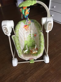 Baby's green and white fisher-price portable swing