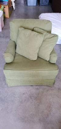 Small green sitting chair with two pillows