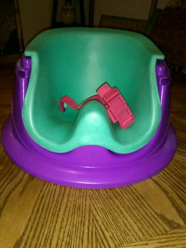 baby's green and pink Bumbo floor seat
