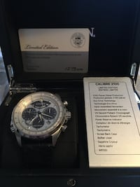 Round silver chronograph watch with black leather strap in box Airdrie, T4B 3L8
