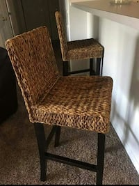 two black framed brown wicker bar stools