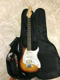Guitar and amp with extra strings and 2 aux cords