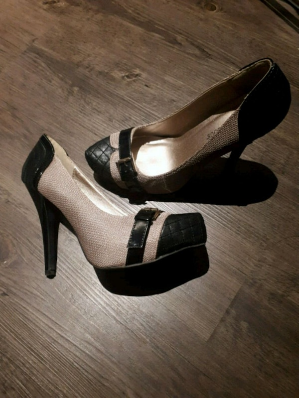 pair of beige-and-black leather platform stilettos