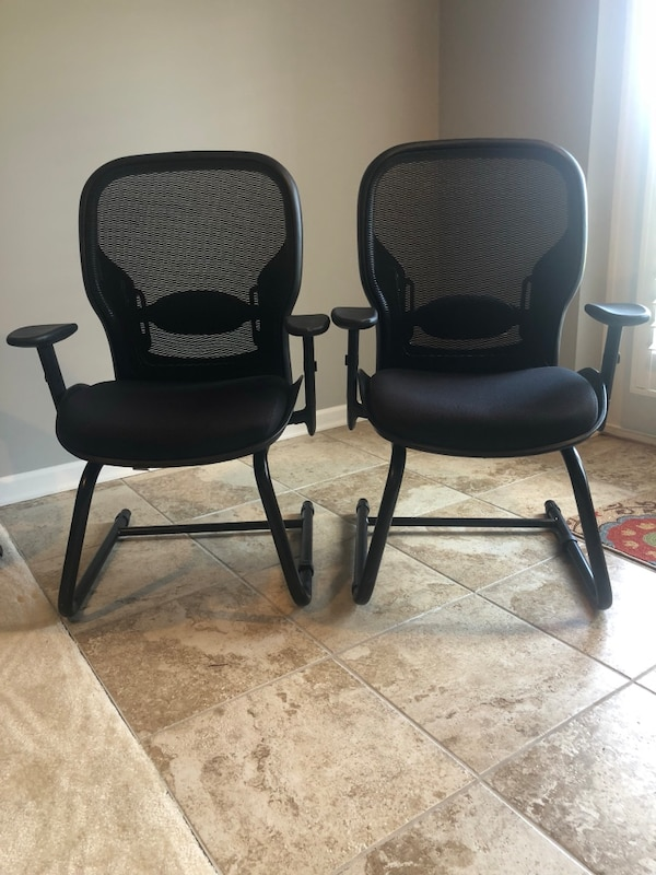 two black-and-gray rolling armchairs