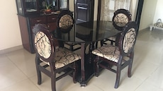 four black wooden framed gray padded dining chairs