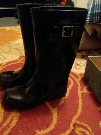 pair of black buckled knee-high boots