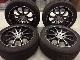 Four gray multi-spoke vehicle wheels and tires