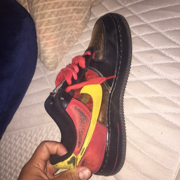 unpaired black and red Nike running shoe