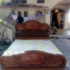 brown wooden bed with yellow and pink floral mattress