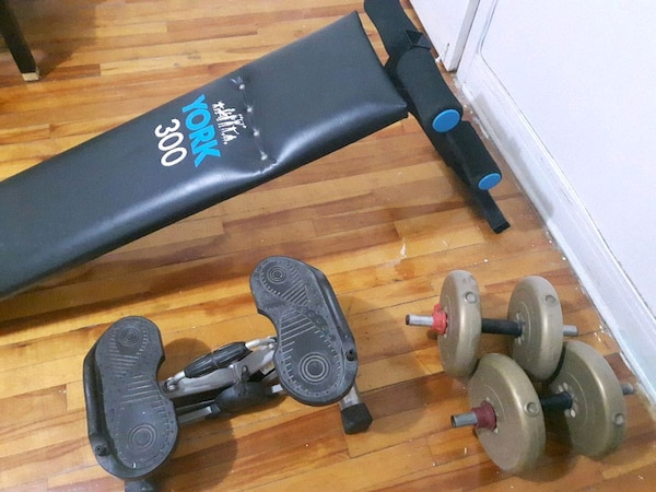 two beige dumbbells and one black mini stepper