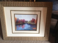 body of water painting with wicker brown frame