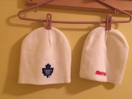 Two white metro and toronto maple leafs knit caps