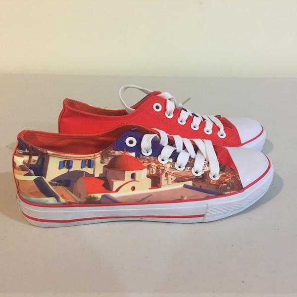 Pair of red-and-white low top sneakers with a Greek design