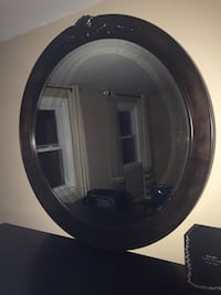 round brown wooden framed wall mirror