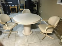 round white wooden pedestal table with four chairs