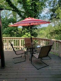 brown metal patio table with chairs and umbrella Newark