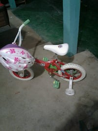 toddler's red and white bike with training wheels