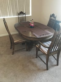 Four brown wooden chairs; brown wooden oval top table Lancaster, 93536