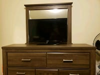 black flat screen TV; brown wooden TV stand Fort Meade