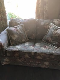 gray and white floral 2-seat sofa with two pillows