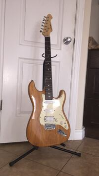 brown electric guitar with black stand Guelph, N1E