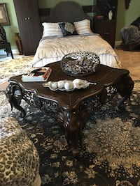 square brown coffee table with elephant heads on corners