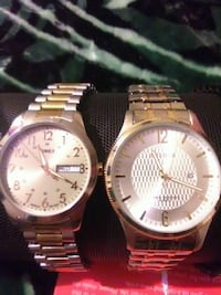 two round silver and gold analog wrist watches