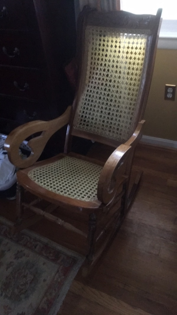 brown wooden framed white padded rocking chair