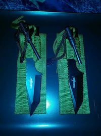 two green paracord-hilt daggers