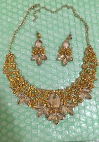 gold-colored beaded necklace with two earrings