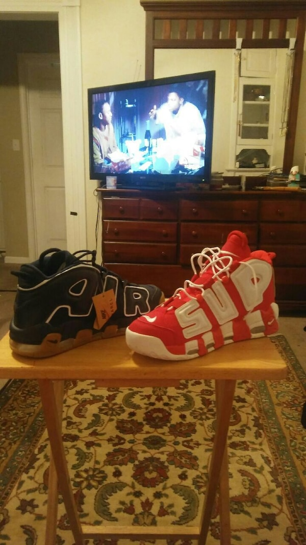 two unpaired black white and gum and red and white Nike Air More Uptempo high top shoes