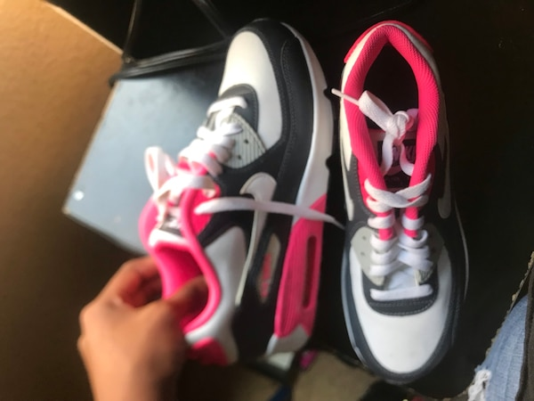 pair of white-and-black Nike basketball shoes