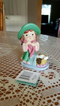 girl wearing green dress ceramic figurine