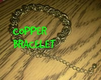 copper-colored chain link bracelet with text overlay Las Vegas, 89121