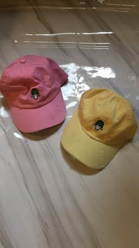 two yellow and pink baseball caps
