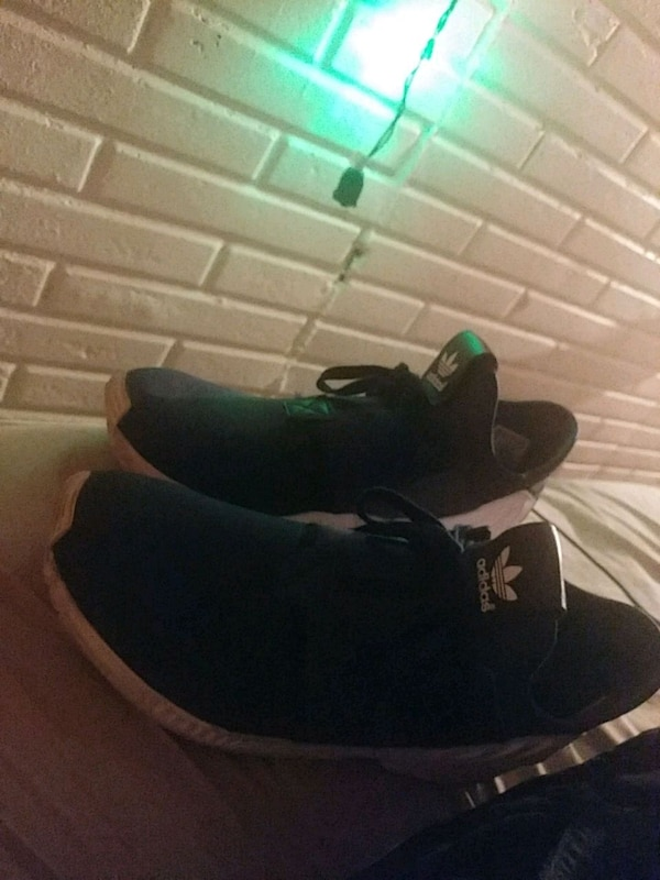pair of black-and-green Adidas sneakers