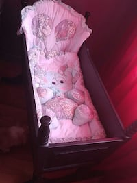 brown wooden cradle with elephant themed mattres