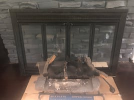 Fireplace doors with grate and ceramic logs.