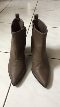 pair of brown leather pointed mid-calf boots