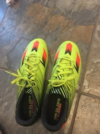 Pair of green-and-black adidas cleats Maple Ridge, V4R 2W6