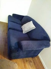 blue suede sofa chair with throw pillow