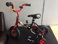 toddler's red and black bicycle with training wheels 536 km