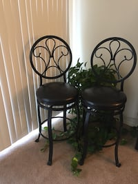 Two black metal framed padded chairs