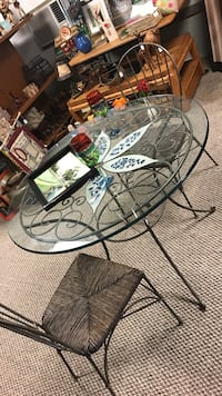 round glass table with black metal frame with two black metal brown padded chair