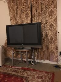 black flat screen TV with brown wooden TV stand Montréal, H3J 1N1