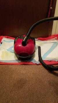 red and black canister vacuum cleaner